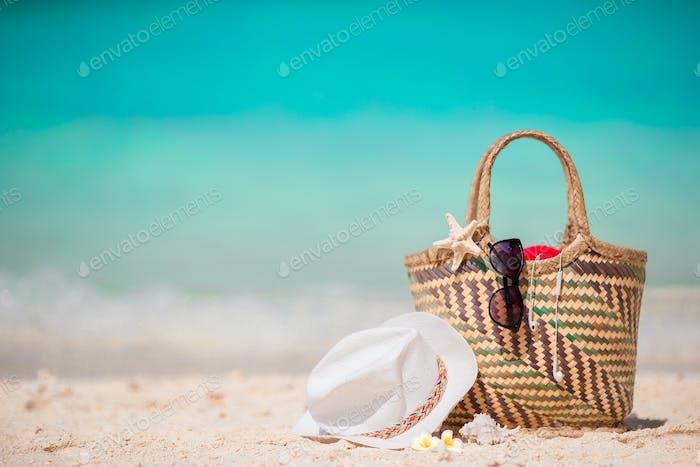 Strohtasche, Fauststern, Kopfhörer, Hut und Sonnenbrille am weißen Strand