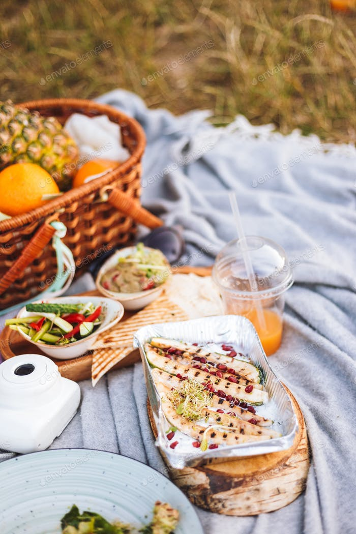 Close up picnic with variety of tasty food and fruits basket on