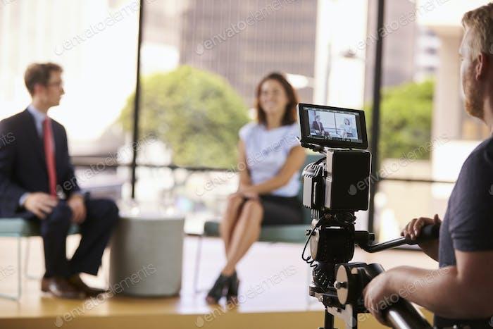 Mann und Frau am Set für ein TV-Interview, Fokus auf den Vordergrund