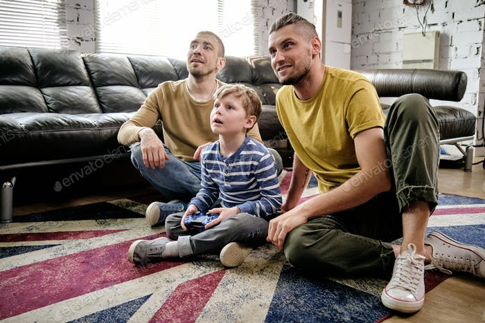 Cute boy and two guys watching television