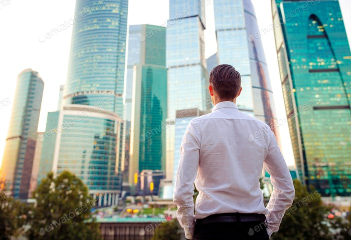 Vista posterior del hombre de negocios mirando en el espacio de copia mientras está de pie contra el rascacielos de vidrio