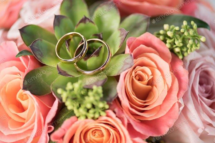 zwei goldene Trauringe auf Blumenstrauß auf Rosen und Sukkulenten, Trauringe und Blumen Konzept