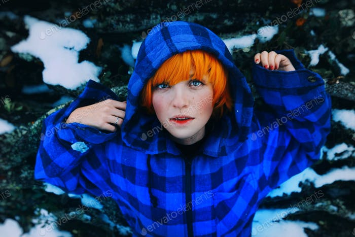 Redhead androgynous woman posing wearing an oversize hoodie