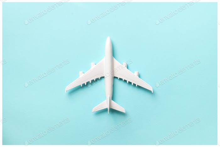 Creative layout. Top view of white model plane, airplane toy on pink pastel background. Flat lay