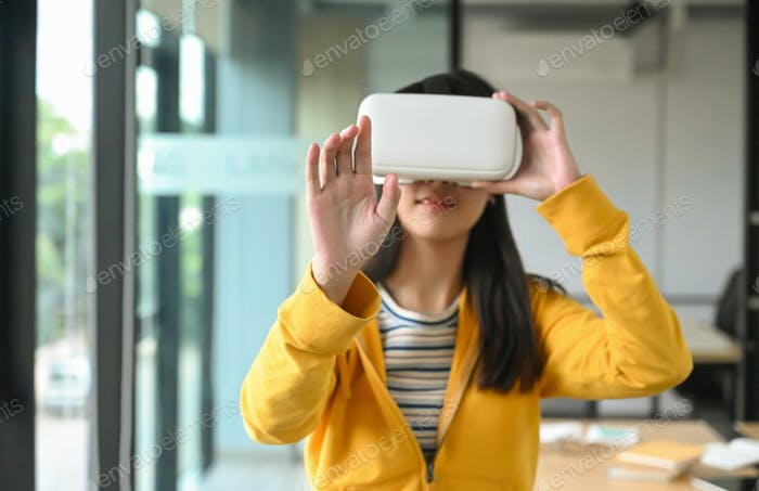 Asian girl is wearing a yellow shirt using VR headset.She pointed hand at front and was smiling.