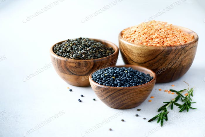 Assorted lentils. Marble, red and black raw organic lentils in wooden bowls with rosemary on grey