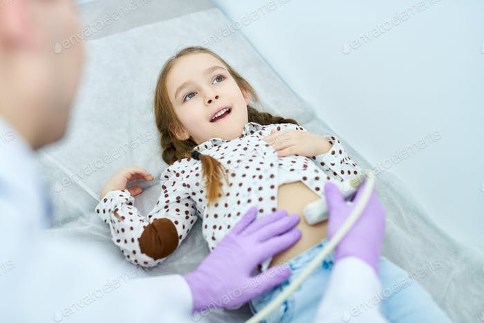 Medical specialist checking up stomach of cute girl