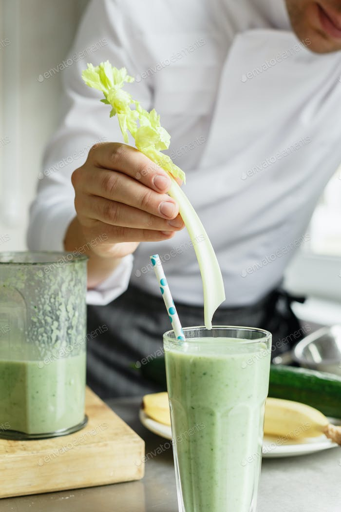 Male chef serving glass with smoothie