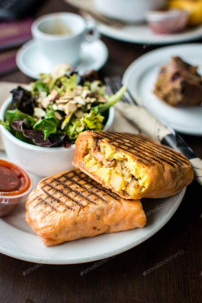 Filling breakfast burrito with salad in a coffeeshop
