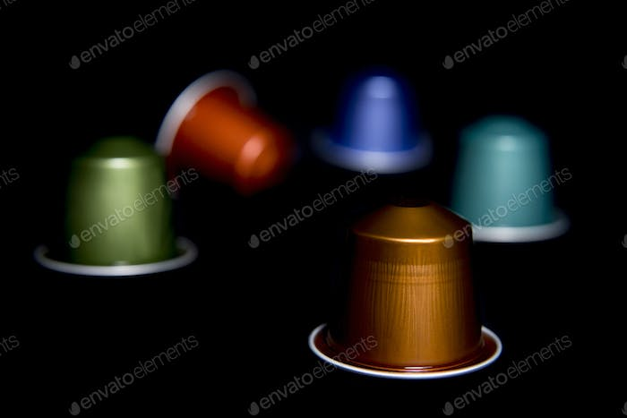 close up of a group of colored and randomly arranged coffee capsules
