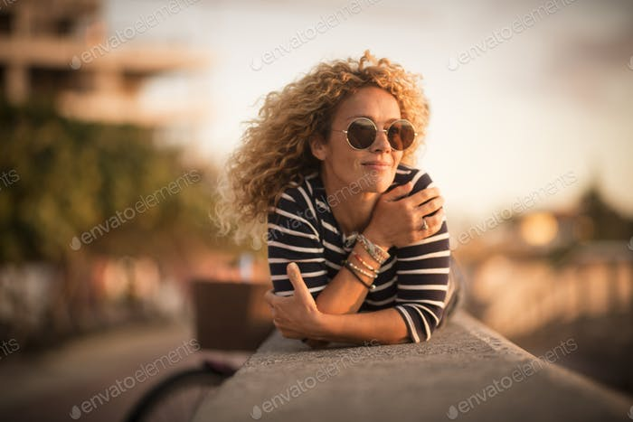 Relaxed and quiet happy beautiful curly blonde woman