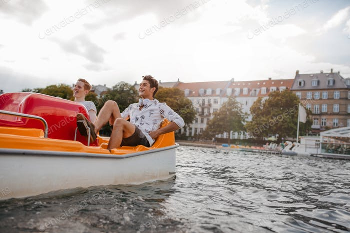 Teenage guys enjoying boating in the lake