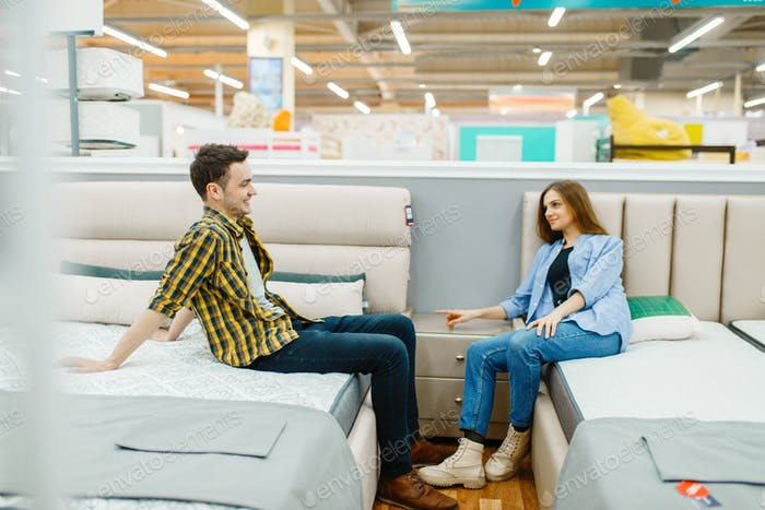 Love couple sitting on beds in furniture store