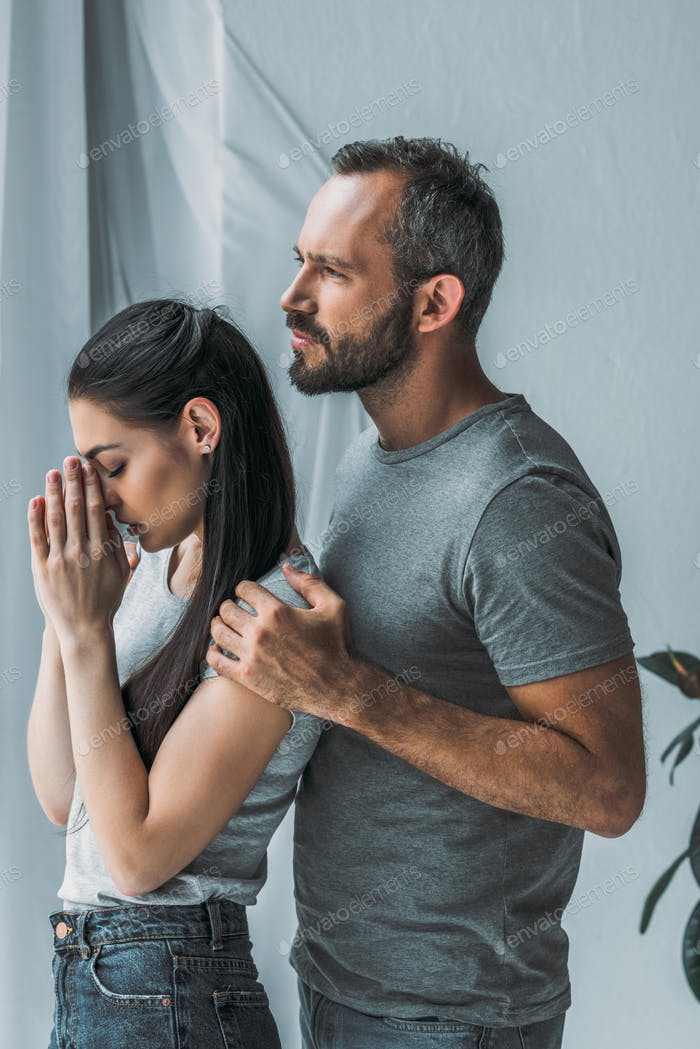 side view of bearded man embracing and supporting sad young woman with hands on face