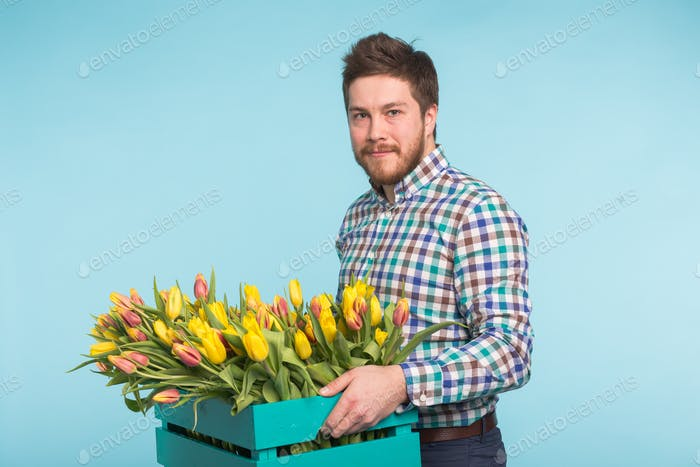 Cheerful handsome man florist holding box of tulips on blue background