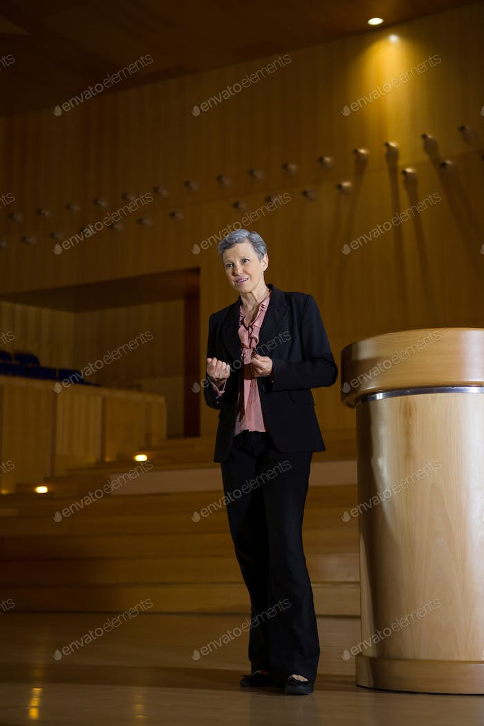 Female business executive gesturing while giving a speech