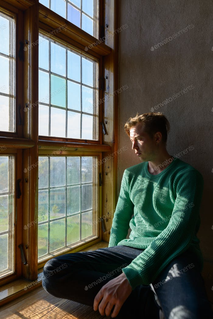 Young handsome Caucasian man sitting in front of closed wooden window with sunlight streaming in