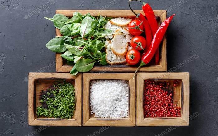 Woman holding cooking ingredients and herbs in wooden box on dark background