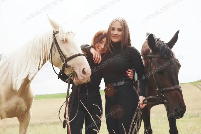 Two young beautiful girls in gear for riding near their horses. They love animals