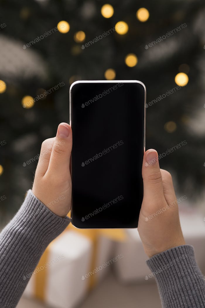 Cellphone in woman hands in over Christmas background