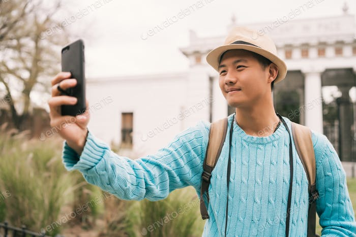 Asian tourist taking a selfie with mobile phone.