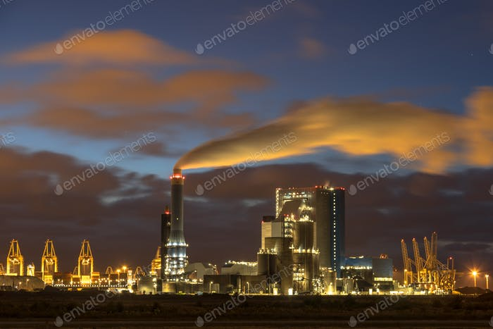 Industrial landscape with illuminated clouds at night