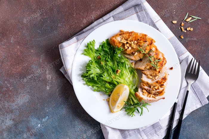 Grilled chicken breast with fresh frize salad and lemon on a plate on dark stone background