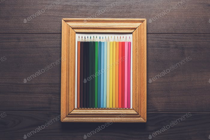 multicolored pencils in a frame over wooden background