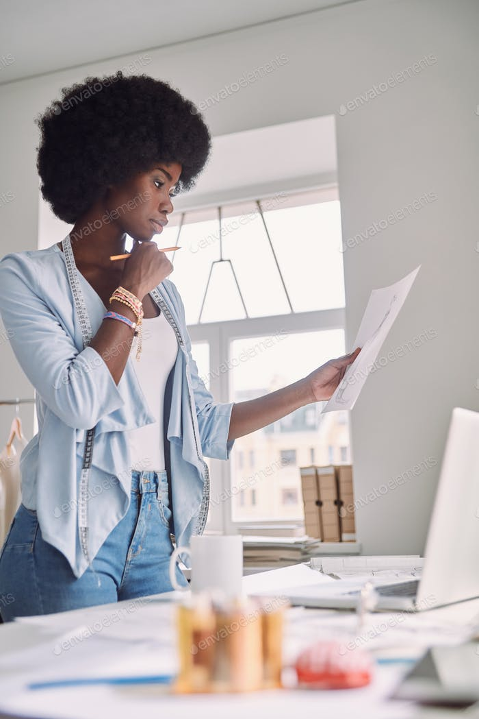 Beautiful young African woman analyzing fashion design sketch while standing near her desk in office