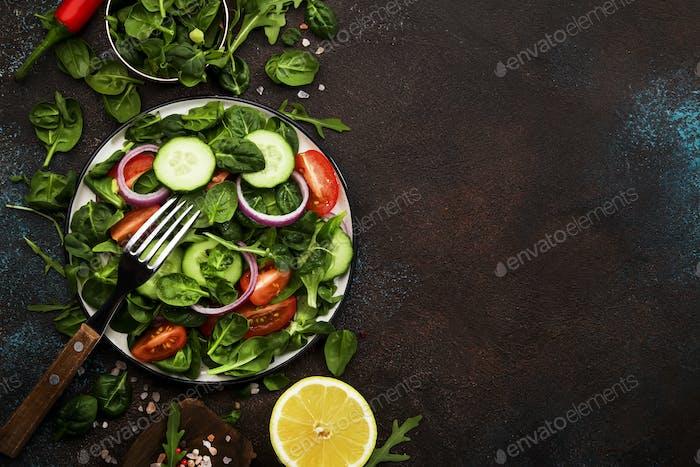 Kirschtomaten, Spinat, Rucola, Gurken, Gewürze und Öl mit Teller