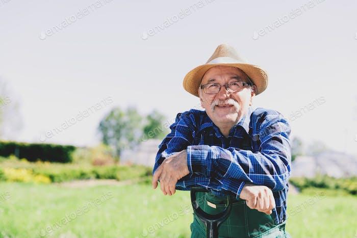 Porträt eines älteren Gärtners stehend in einem Garten