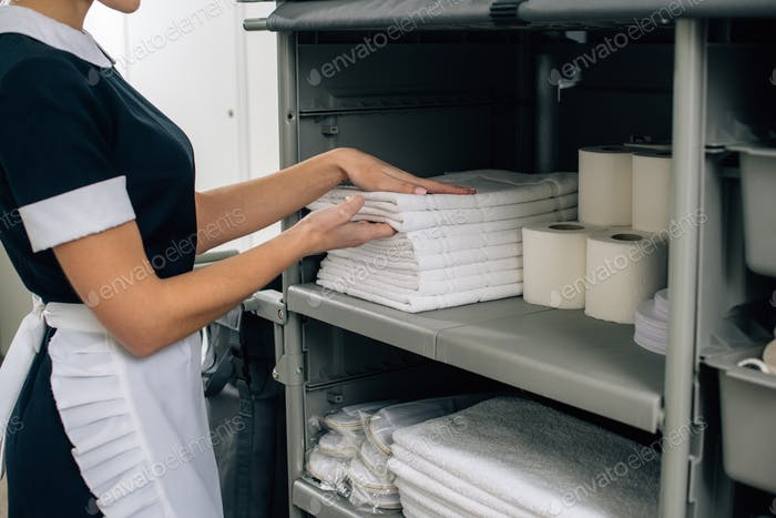 cropped shot of maid in uniform taking towels from shelf of housekeeping cart