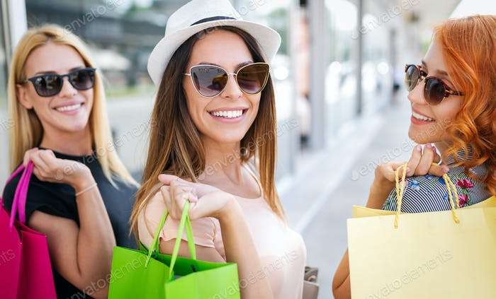 Happiness, friends, shopping and fun concept-smiling young women with shopping bags