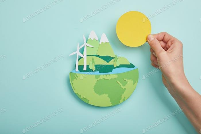 Draufsicht einer Frau mit Papierschnitt Sonne und Planet mit erneuerbaren Energiequellen auf Türkis