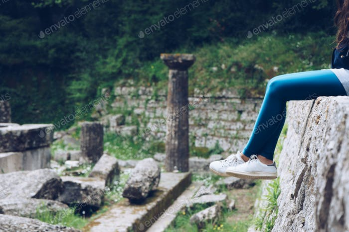 Girl is sitting on remains of a Doric temple, Mon Repos park, Co