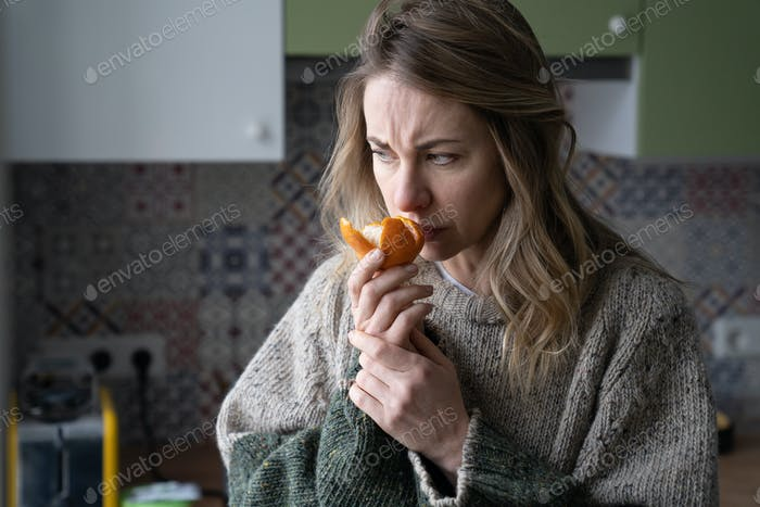 Sick woman trying to sense smell of fresh tangerine orange, has symptoms of Covid-19, corona virus