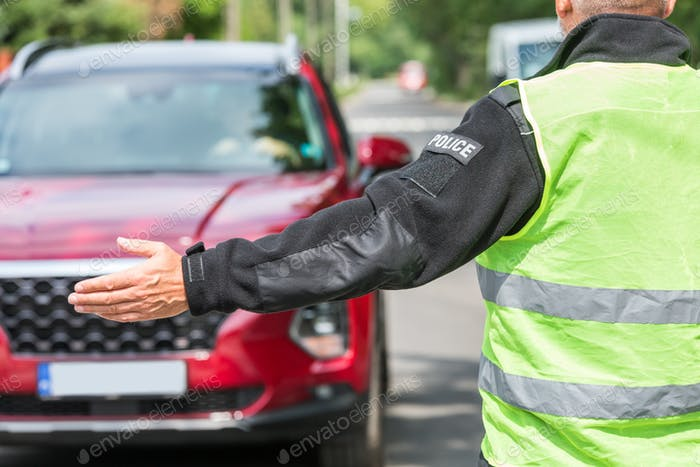 Policeman in a reflective vest extends his hand to stop a red car