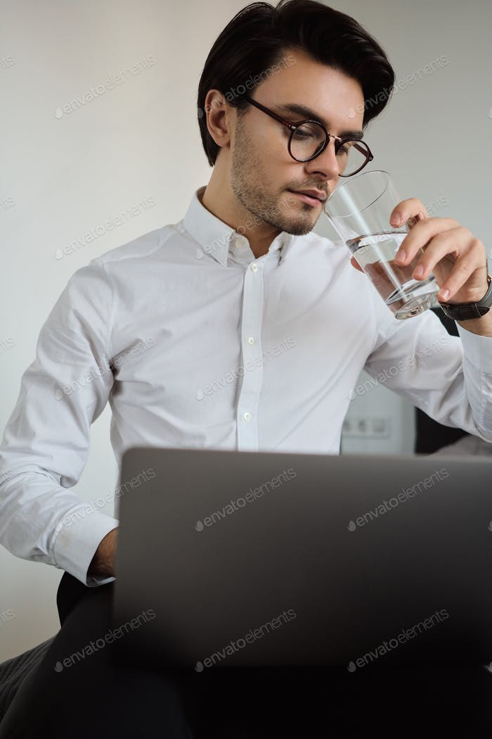 Young man in white shirt and eyeglasses sitting on bed dreamily working on laptop and drinking water