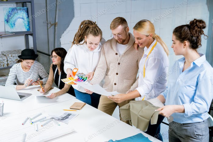 Group of creative fashion designers discussing colors, textile and sketches