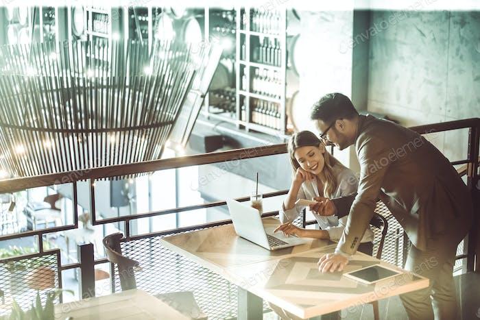 Geschäftskollegen lachen und arbeiten beim Blick auf den Laptop
