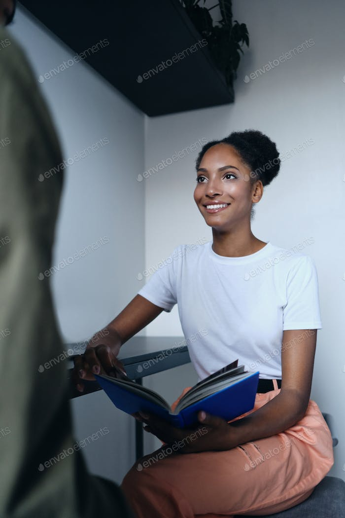 Pretty smiling African American woman joyfully talking with co worker in modern co-working space
