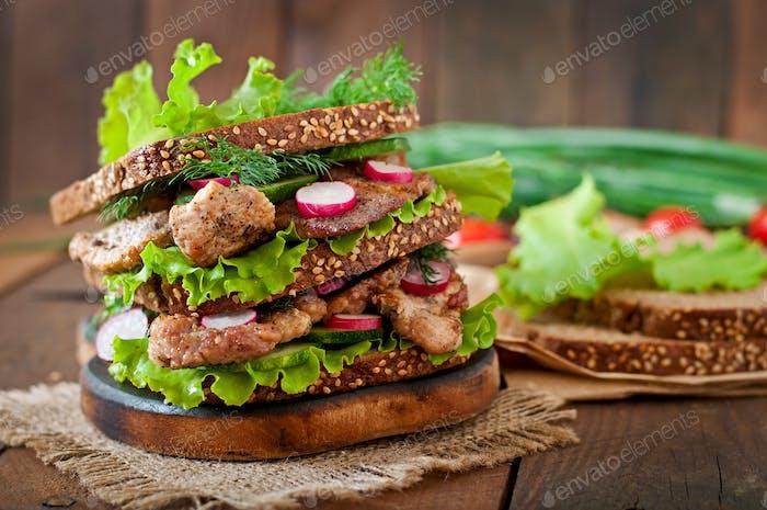 Sandwich mit Fleisch, Gemüse und Scheiben Roggenbrot