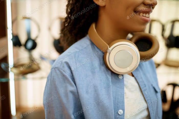 Young woman buying headphones in acoustics store