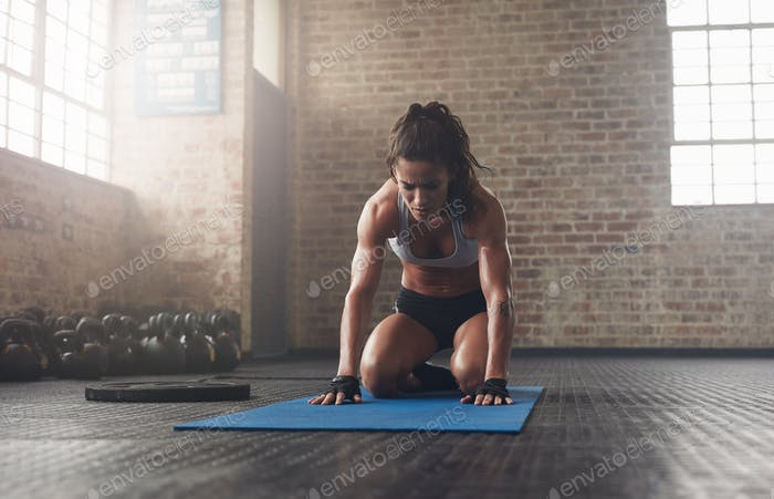 Young woman doing a forward bend exercise on fitness mat