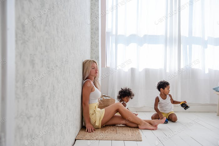 Tired of domestic life Young Caucasian blond mother with her African American son and daughter