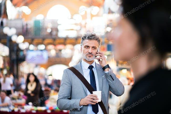Reifer Geschäftsmann mit Smartphone in einer Stadt.