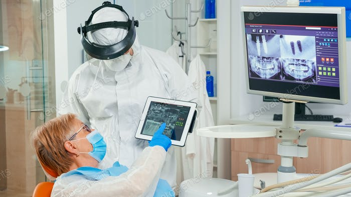 Stomatologist with face shield reviewing x-ray pointing on tablet