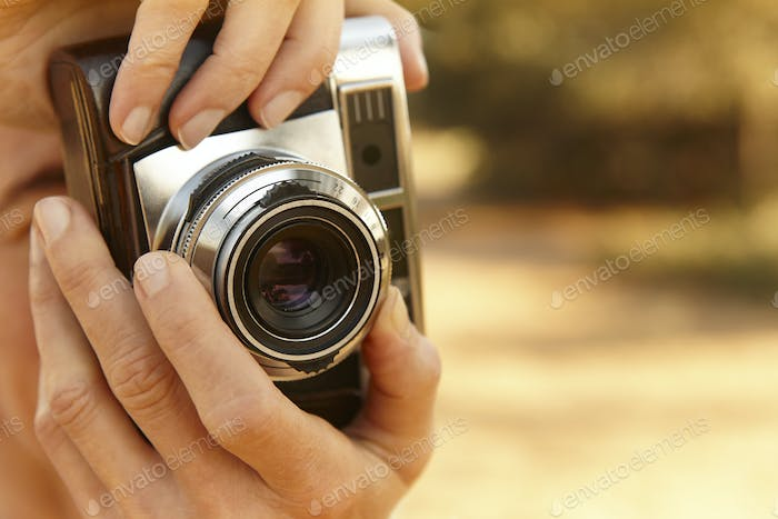 Woman taking pictures with vintage camera. Travel background