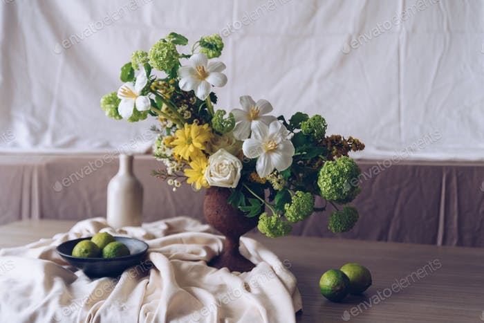 Still life with a beautiful bouquet of flowers, candles and lime