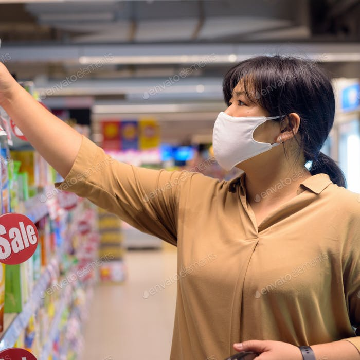 Overweight Asian woman with mask for protection from corona virus outbreak shopping inside